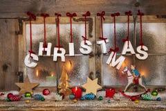 Weihnachtsfensterdekoration im Freien mit roten Kerzen und Text Stockbild