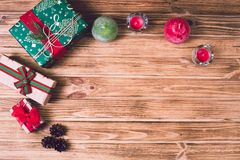 Weihnachtsferiengeschenkkasten auf verzierter festlicher Tabelle mit Kiefernkegeln auf hölzernem Hintergrund Stockbilder