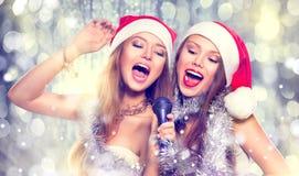 Weihnachtsfest Drei recht reizvolle Mädchen, die Weihnachtsmann-, Katze- und Häschenkleidung tragen Singende Schönheitsmädchen Stockbild