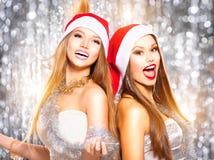Weihnachtsfest Drei recht reizvolle Mädchen, die Weihnachtsmann-, Katze- und Häschenkleidung tragen Singende Schönheitsmädchen Lizenzfreie Stockfotografie