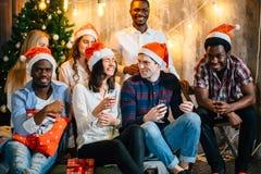 Weihnachtsfestfreunde am Haben des Getränks und des Spaßes stockfotos