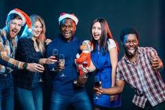 Weihnachtsfestfreunde am Haben des Getränks und des Spaßes stockfoto
