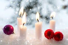 Weihnachtsflitter ein brennende Kerzen im Schnee stockfotos