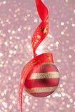 Weihnachtsflitter mit rotem Band auf Konfettihintergrund Lizenzfreie Stockfotos
