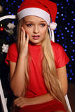 Weihnachtsfoto des netten kleinen blonden Mädchens in Sankt-Hut und im roten Kleid Stockfotos