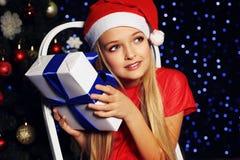 Weihnachtsfoto des netten kleinen blonden Mädchens in Sankt-Hut und im roten Kleid Lizenzfreie Stockfotografie