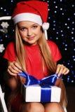 Weihnachtsfoto des netten kleinen blonden Mädchens in Sankt-Hut und in rotem Kleid, die eine Geschenkbox auf dem backgroud Feiert Stockbild