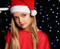 Weihnachtsfoto des netten kleinen blonden Mädchens in Sankt-Hut und in rotem Kleid, die eine Geschenkbox auf dem backgroud Feiert Lizenzfreie Stockfotos
