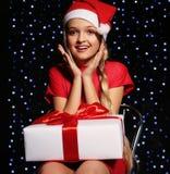 Weihnachtsfoto des netten kleinen blonden Mädchens in Sankt-Hut und in rotem Kleid, die eine Geschenkbox auf dem backgroud Feiert Lizenzfreies Stockbild