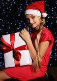 Weihnachtsfoto des netten kleinen blonden Mädchens in Sankt-Hut und in rotem Kleid, die eine Geschenkbox halten Stockfotografie