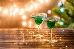 Weihnachtsfoto von zwei Weingläsern mit grünem Cocktail Stockfotografie