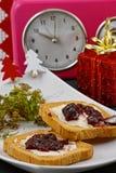Weihnachtsfrühstück und -uhr Stockbild