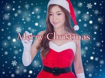 Weihnachtsfrau, die frohe Weihnachten schreibend lächelt Lizenzfreies Stockfoto