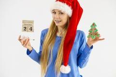 Weihnachtsfrau, die Kalender und Baum hält Stockfoto