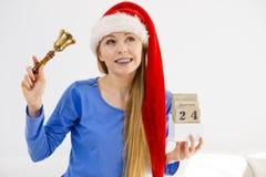 Weihnachtsfrau, die Kalender und Glocke hält Stockfotografie