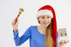 Weihnachtsfrau, die Kalender und Glocke hält Stockfoto