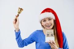 Weihnachtsfrau, die Kalender und Glocke hält Lizenzfreie Stockfotos