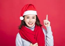 Weihnachtsfrau, die Sankt-Hut trägt und oben zeigt Lizenzfreie Stockfotografie