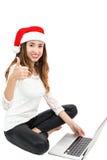 Weihnachtsfrau mit einem Laptop, der Daumen aufgibt Lizenzfreie Stockbilder