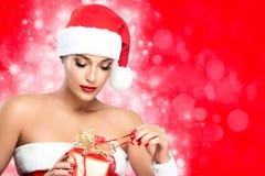 Weihnachtsfrau in Sankt-Kleidung, die Geschenk auspackt Stockbild