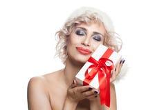 Weihnachtsfrau in Santa Hat mit weißem Weihnachtsgeschenk Stockbilder