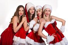 Weihnachtsfrauen in Santa Helper-Hüten Stockbilder