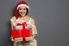 Weihnachtsfrauenporträt, das Weihnachtsgeschenk hält Lächelnder glücklicher g lizenzfreie stockfotografie
