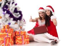 Weihnachtsfreundinnen mit Laptop. Lizenzfreie Stockbilder