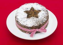 Weihnachtsfrucht-Kuchen auf einem roten Hintergrund Stockbild