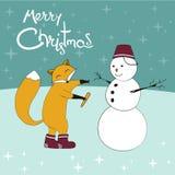 Weihnachtsfuchs mit einer Karotte in einer Tatze und in einem Schneemann, die auf seinen Nasensatz warten Lizenzfreie Stockfotografie