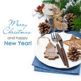 Weihnachtsgedeck mit hölzernen Dekorationen über Weiß Stockfotos