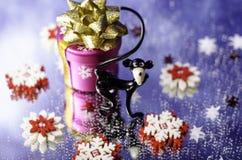 Weihnachtsgeschenk, der Affe und die roten und weißen Schneeflocken Stockfotografie