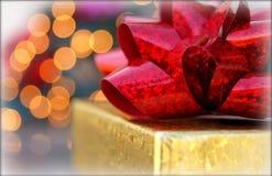 Weihnachtsgeschenk eingewickelt im Gold mit rotem Bogen Stockbild