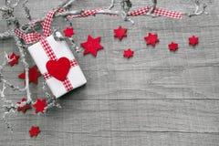 Weihnachtsgeschenk eingewickelt im roten Papier auf einem hölzernen Hintergrund Stockbild