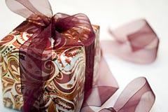 Weihnachtsgeschenk eingewickelt mit rotem Paisley-Papier Lizenzfreies Stockbild