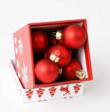 Weihnachtsgeschenk gefüllt mit roten Weihnachtsbällen Stockbilder