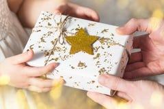 Weihnachtsgeschenk, Hände, die weißes Geschenk mit goldenem Stern halten Stockfotos