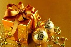 Weihnachtsgeschenk im Goldkasten mit Bogen Stockfotografie
