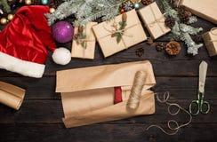 Weihnachtsgeschenk im Packpapier auf einem Holztisch Lizenzfreies Stockfoto