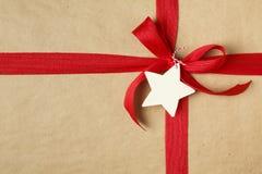 Weihnachtsgeschenk mit Bogen und leeres Geschenk etikettieren Einfacher aufbereiteter Packpapierhintergrund und natürliches Jutef Stockbild