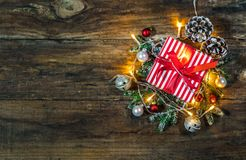 Weihnachtsgeschenk mit festlicher Dekoration auf hölzernem Hintergrund Stockfotos