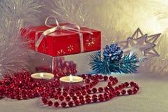 Weihnachtsgeschenk mit Kerzen und einem weißen Lametta Lizenzfreie Stockbilder