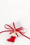 Weihnachtsgeschenk mit rotem Band auf einem weißen Schneehintergrund Lizenzfreies Stockbild