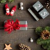 Weihnachtsgeschenk mit rotem Band, Weihnachtskalender, Kiefernniederlassungen, Kegel und Weihnachtsdekorationen Stockfotos