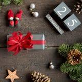 Weihnachtsgeschenk mit rotem Band, Weihnachtskalender, Kiefernniederlassungen, Kegel und Weihnachtsdekorationen Stockfotografie