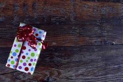 Weihnachtsgeschenk mit rotem Bogen im Holztisch Stockbild