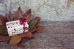 Weihnachtsgeschenk mit rotem Bogen im Holztisch Bunter Hintergrund der trockenen Herbstblätter Stockbild