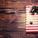 Weihnachtsgeschenk mit roter Farbe auf dunklem hölzernem Hintergrund in VI Stockfoto