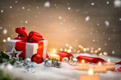 Weihnachtsgeschenk mit Schnee, Kerzen und Verzierungen Lizenzfreies Stockfoto