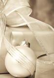 Weihnachtsgeschenk und -kugel im Sepia Stockfotos